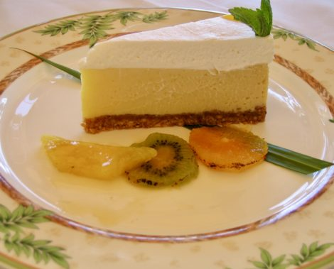 Cashew crusted piece of key lime pie with fruit garnish.