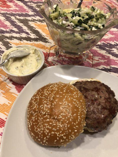 A lamb burger with bowls of lemon Oregano Aioli and Cucumber Feta Relish