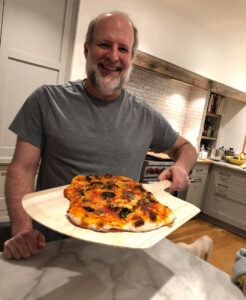 Mark Katzman holding pizza.