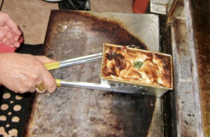 Removing baked spanakopita from oven at Cafe Nova