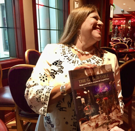Suzanne holding a copy of The Gilded Table